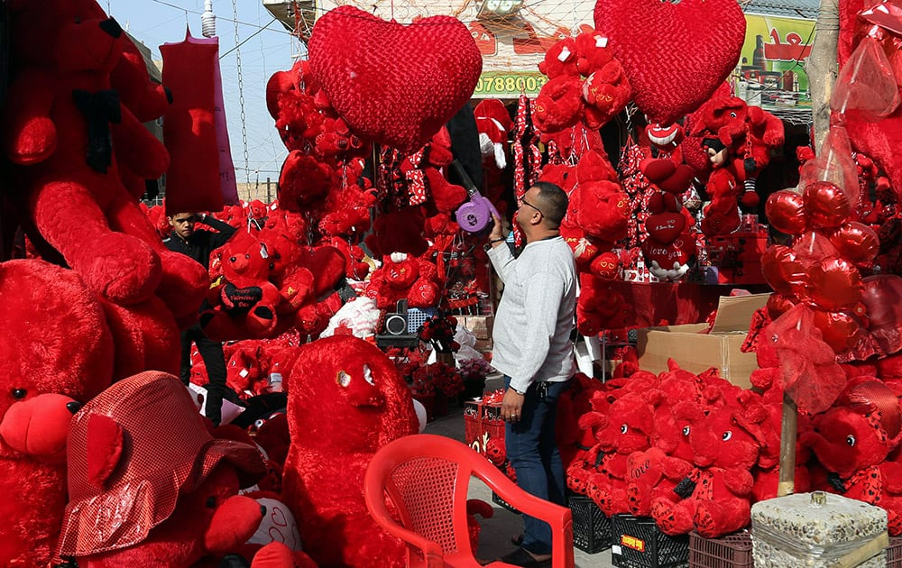 A shop owner cleans his merchandise ahead of Valentine's Day at the Karrada neighborhood of Baghdad, Iraq.