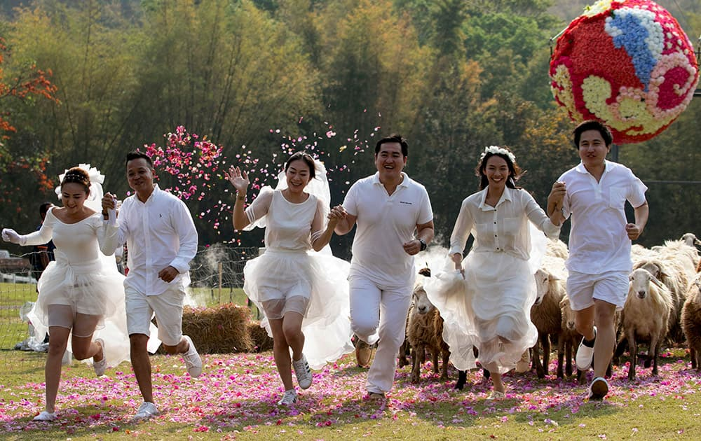 Brides and grooms run away from a giant flower ball as a part of an adventure-themed wedding ceremony in Ratchaburi Province, Thailand, on the eve of Valentine's Day.