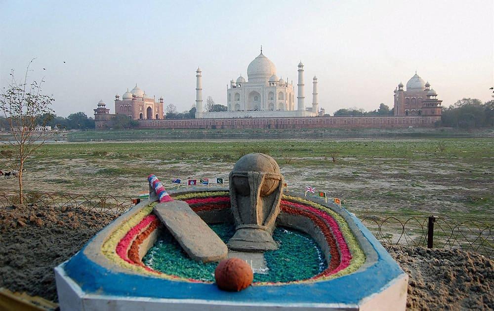 Sand artist Sudarshan Patnaik creates a sand image on ICC World Cup 2015 near the Taj Mahal in Agra.