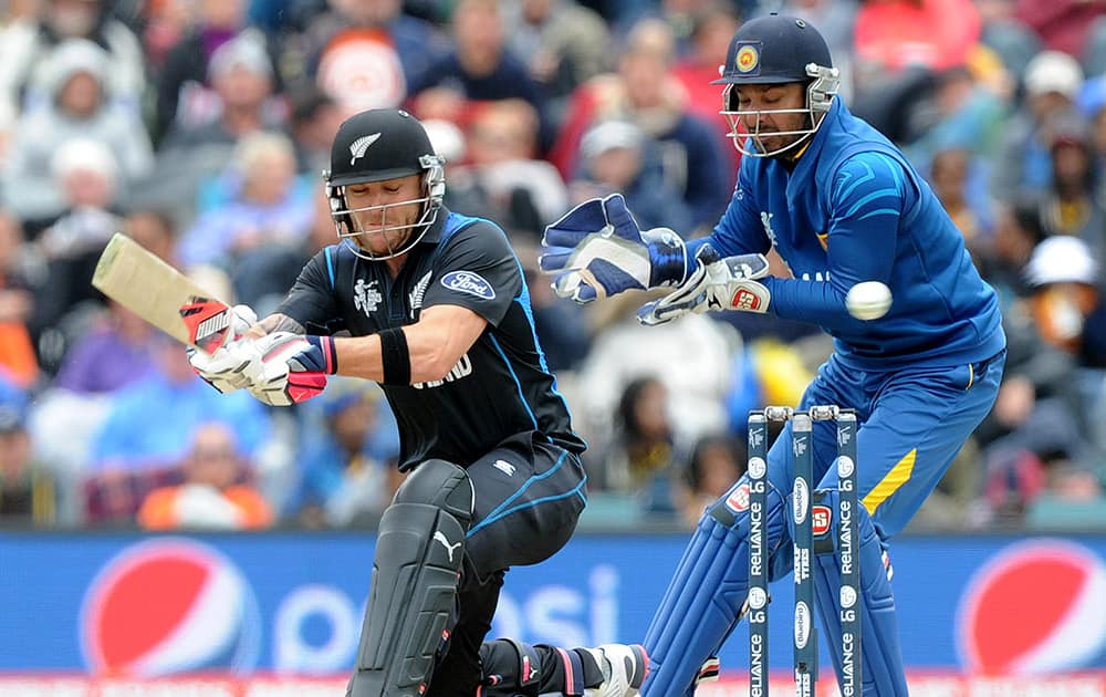 New Zealand's Brendon McCullum, left, sweeps the ball in front of Sri Lanka's Kumar Sangakkara during the opening match of the Cricket World Cup at Christchurch, New Zealand.
