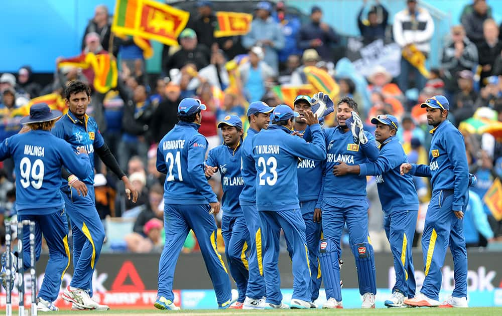 Sri Lanka's Suranga Lakmal and Kumar Sangakkara, celebrate with teammates after combining to take the wicket of New Zealand's Martin Guptill for 49 runs during the opening match of the Cricket World Cup at Christchurch, New Zealand.