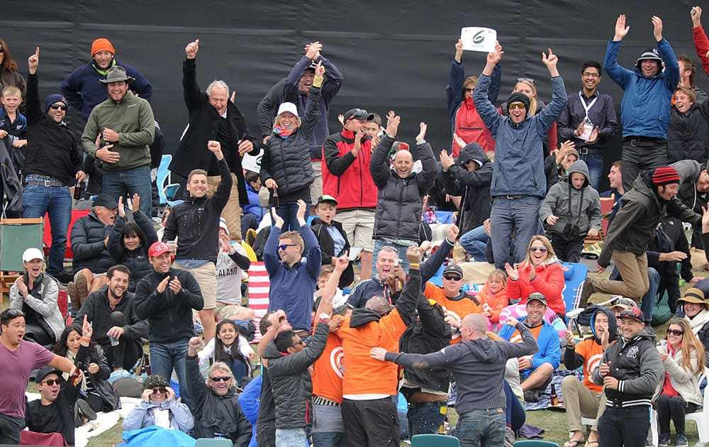 The crowd celebrate after a fan, bottom center with back to the camera, made a one-handed catch off a six hit by New Zealand against Sri Lanka during the opening match of the Cricket World Cup at Christchurch, New Zealand.
