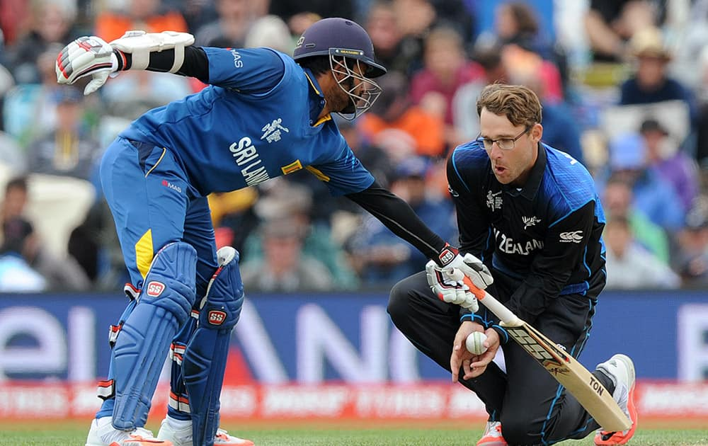 New Zealand's Daniel Vettori, right, catches out, off his own bowling, Sri Lanka's Tillakaratne Dilshan for 24 runs as Lahiru Thirimanne, left, reaches for his crease during the opening match of the Cricket World Cup at Christchurch, New Zealand.