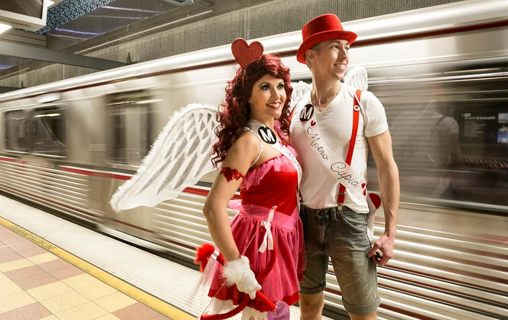 Performers Shauna Hackney and Jared Hansen, dressed as 'Metro Cupids,' await the 'Speed Dating' car on the Red Line train heading to North Hollywood in Los Angeles.