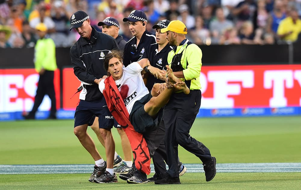 A pitch invader is carried off the field by security during their Cricket World Cup pool A match between Australia and England in Melbourne, Australia.