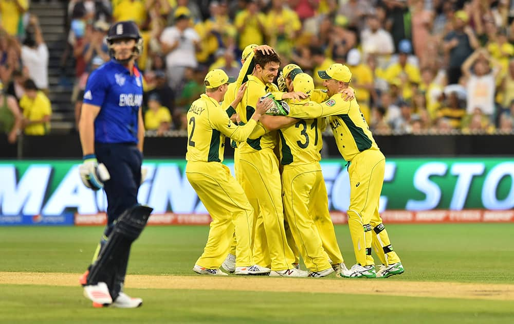 England's Jos Buttler walks off the field past Australia's Mitchell Marsh, as he celebrates with team mates during their Cricket World Cup pool A match in Melbourne, Australia.