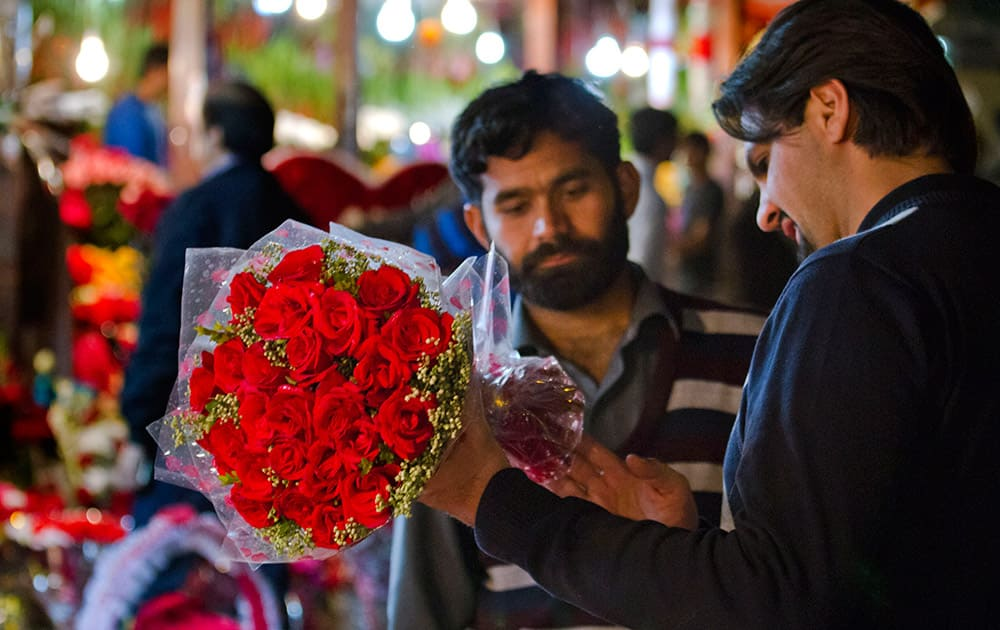 A Pakistani buys a bouquet of flowers at a market on Valentine's Day in Islamabad, Pakistan.