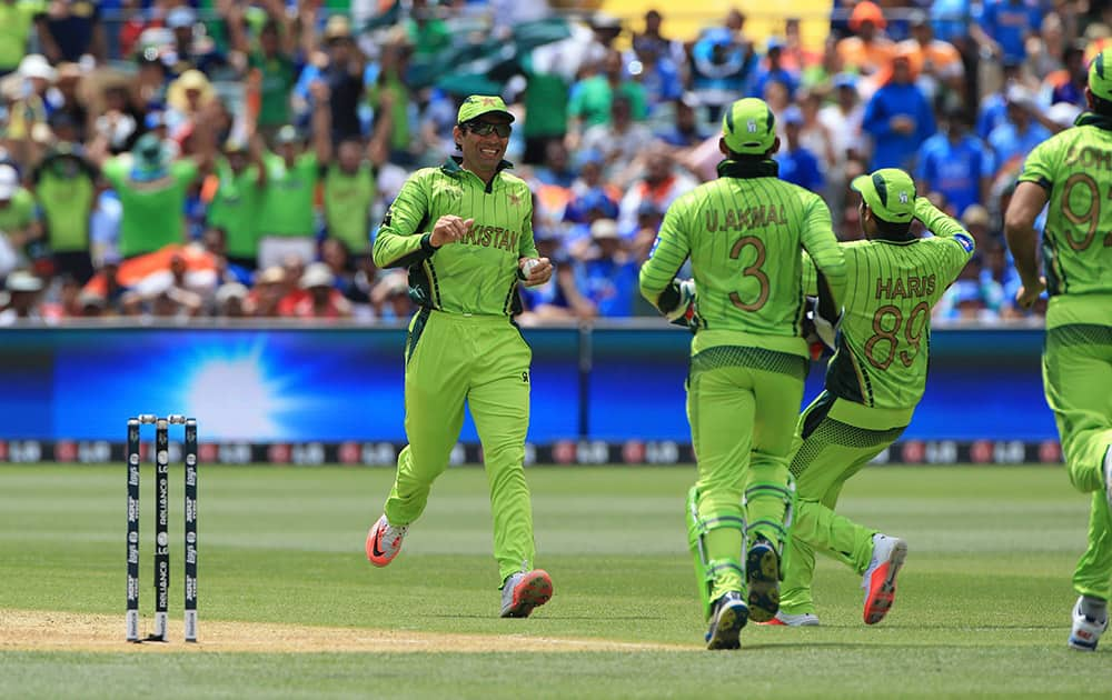 Pakistan captain Misbah-ul-Haq, left, rushes to celebrate after taking a catch to dismiss India's Rohit Sharma during the World Cup Pool B match in Adelaide.