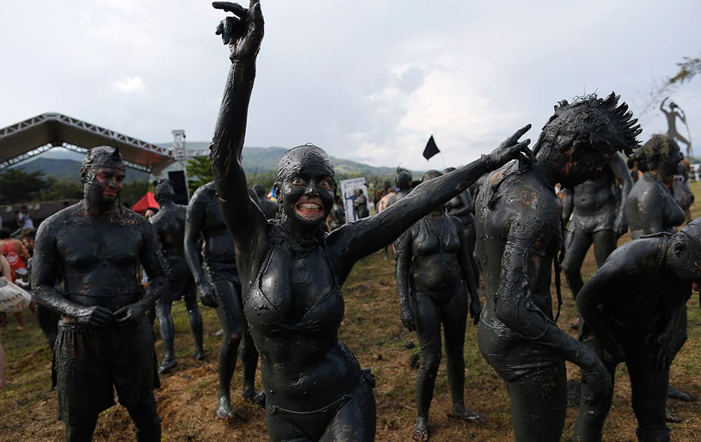 A woman, covered in mud, dances during the traditional 'Bloco da Lama' or 'Mud Block' carnival party, in Paraty, Brazil.