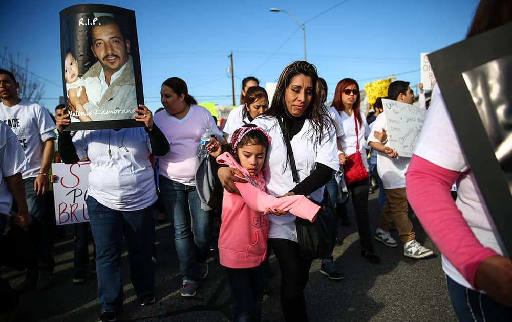 Linda Zambrano and Gina Ruiz, 5, relatives of Antonio Zambrano-Montes, march during for Zambrano-Montes, in Pasco, Wash.