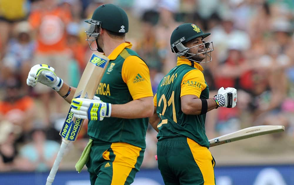 South Africa's Jean-Paul Duminy, celebrates along with teammate David Miller after Duminy made 100 runs against Zimbabwe during their Cricket World Cup pool B match at Hamilton, New Zealand.