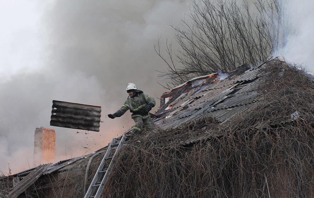 A firefighter dismantles a roof to extinguish a building on fire after shelling between Russian-backed separatists and Ukrainian government in residential area of the town of Artemivsk.