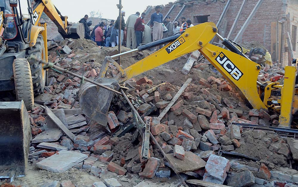Rescuers use machinery to remove the debris after a building that was under construction collapsed overnight, in the town of Mughalsarai, about 300 kilometers (186 miles) southeast of Uttar Pradesh's state capital of Lucknow.