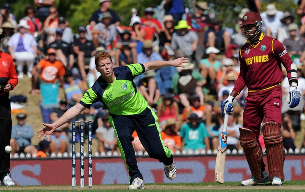 Ireland's Kevin O'Brien, left, reaches to field a ball off his own bowling as West Indies' Marlon Samuels holds his ground during their Cricket World Cup pool B match at Nelson, New Zealand.