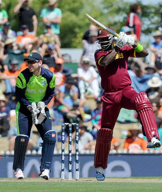 West Indies' Darren Sammy, right, drives the ball as Ireland's wicketkeeper Gary Wilson readies to field during their Cricket World Cup pool B match at Nelson, New Zealand.