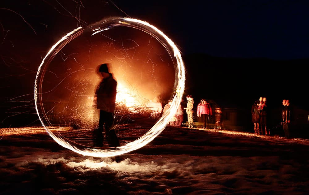 This photo taken with a long exposure photo, a silhouetted child spins a ball of fire during rituals in celebration of Mesni Zagovezni (Shrovetide) in the village of Lozen near the capital Sofia.