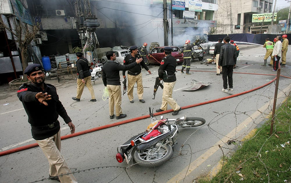 Pakistani police officers cordon off the site of a bombing in Lahore, Pakistan. An apparent suicide bombing killed many people outside a police complex in eastern Pakistan, officials said, in a rare attack on the relatively peaceful city of Lahore.