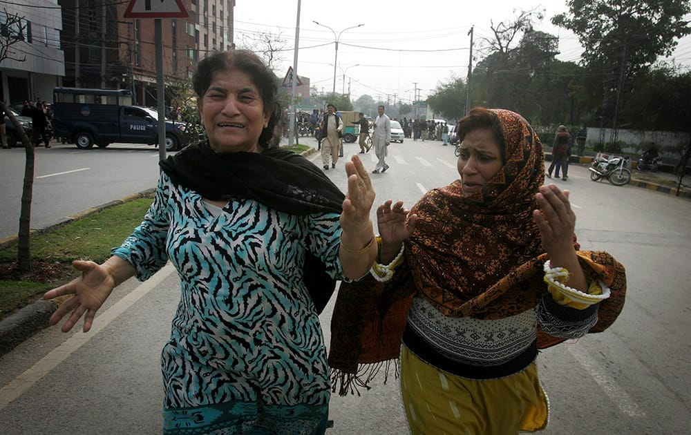 Pakistani women run following a bombing in Lahore, Pakistan.