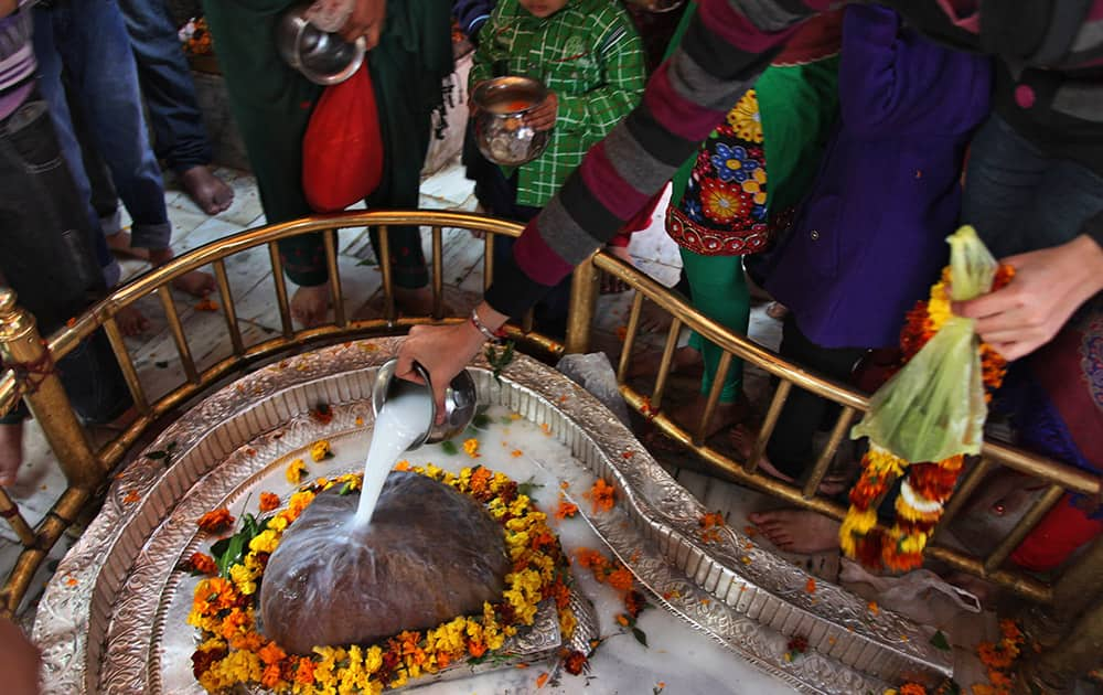 Devotees pour milk on a Shivling, an idol symbolic of Hindu god Shiva, at the Aap Shambhu Lord Shiva temple during