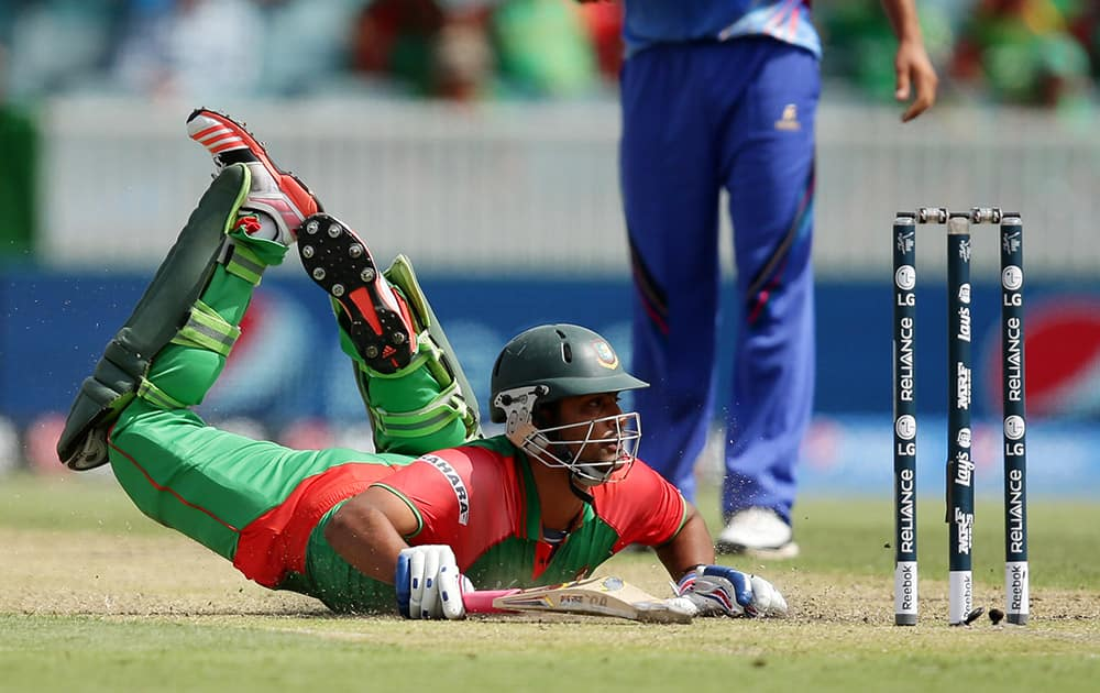 Bangladesh batsman Iqbal Tamim dives to make his ground during their Cricket World Cup Pool A match against Afghanistan in Canberra, Australia.