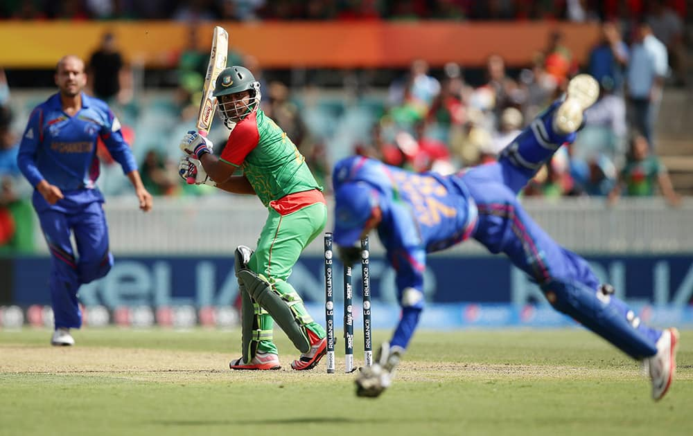 Bangladesh batsman Iqbal Tamim watches as Afghanistan's wicketkeeper Zazai Afsar, takes a catch to dismiss him for 19 run during their Cricket World Cup Pool A match in Canberra, Australia.
