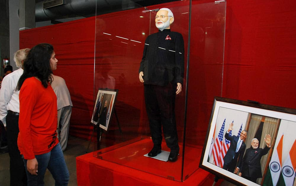 A visitor looks at Prime Minister Narendra Modi's controversial pinstripe monogrammed bandhgala suit during its auction in Surat.