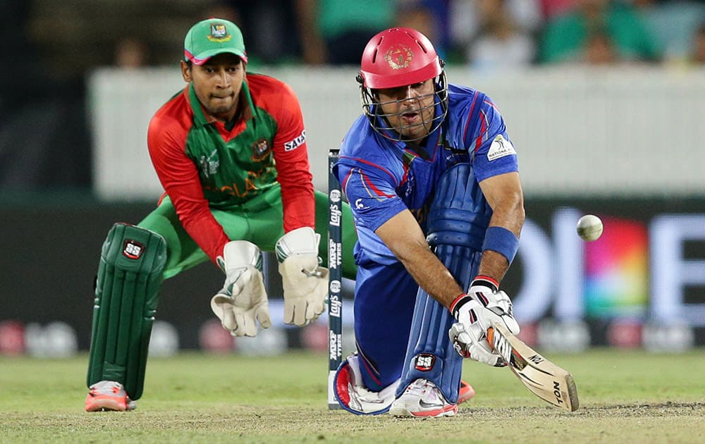 Afghanistan batsman Mohammad Nabi plays a sweep shot as Bangladesh wicketkeeper Mushfiqur Rahim looks on during their Cricket World Cup Pool A match in Canberra, Australia.
