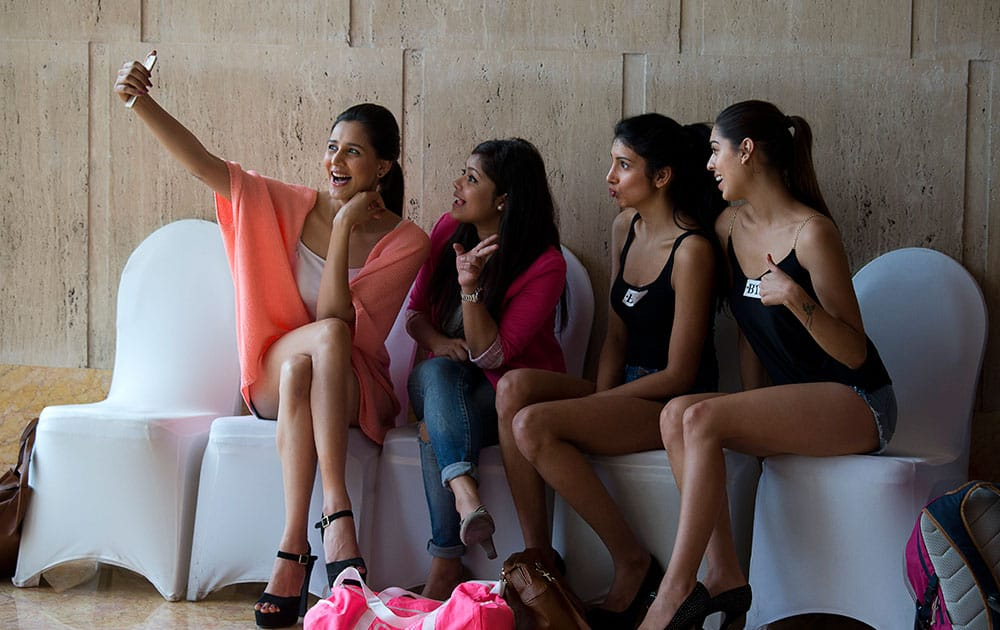 An aspirant takes a selfie along with others during auditions for the India Fashion Week (IFW) in New Delhi, India.