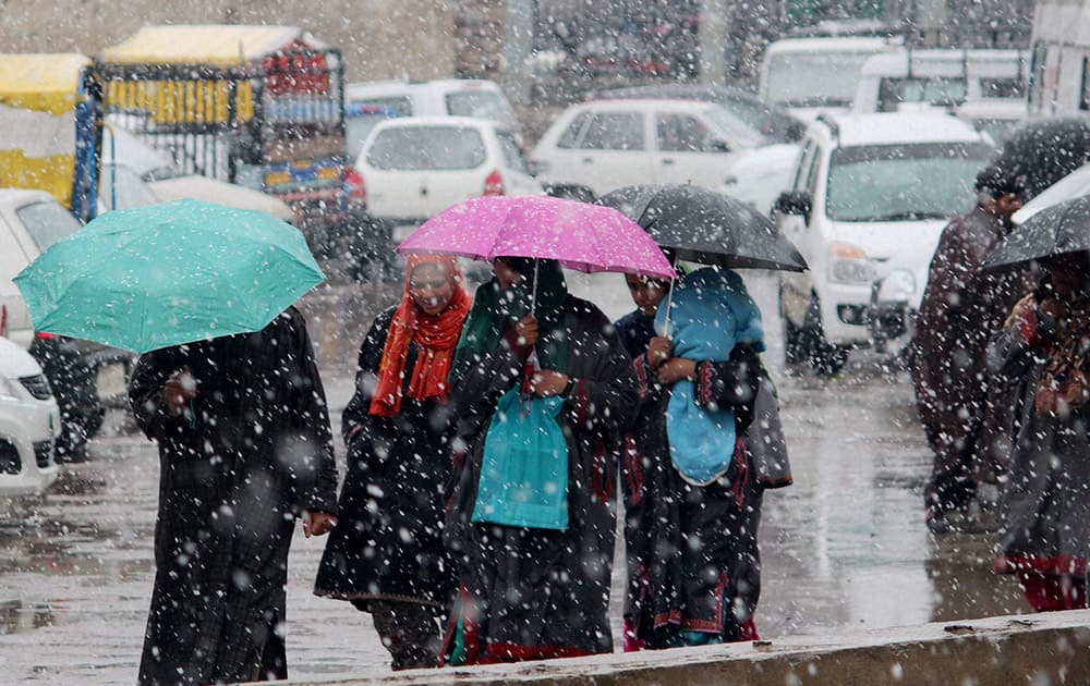 People on the streets with their umbrellas after heavy snowfall gripped Srinagar.
