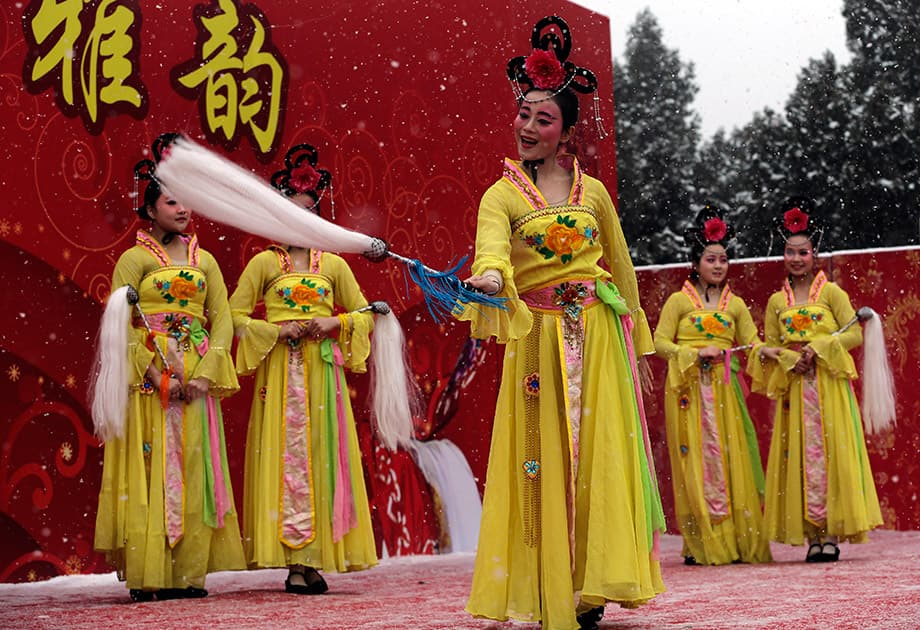 Chinese performers dressed in traditional costumes participate in a cultural dance in the snow on stage at Ditan Park during a temple fair for a Lunar New Year celebration, in Beijing.