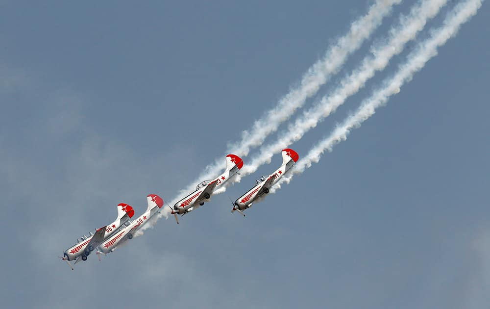 Russian aerobatic team Yakovlev performs a maneuver on the third day of Aero India 2015 at Yelahanka air base in Bangalore.