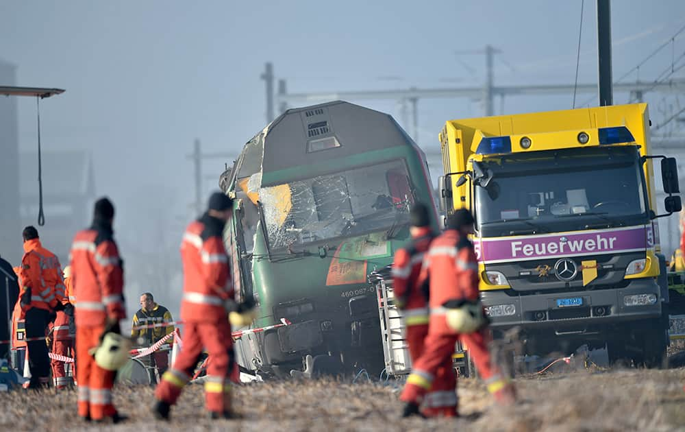 Rescue service men and firemen work at a derailed train a the accident site in Rafz, canton Zurich, Switzerland.