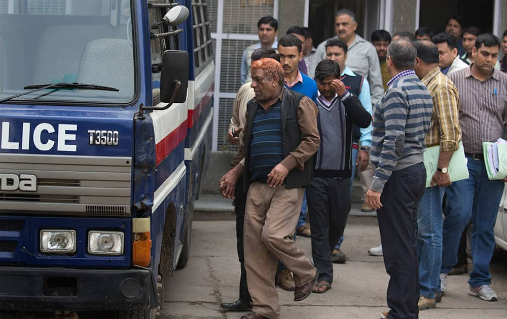 Police in civil clothing escort two alleged suspects, center and center right, who are among the seven persons in an oil espionage case, to a police van to be produced in a court from the Delhi Crime Branch unit, in New Delhi.