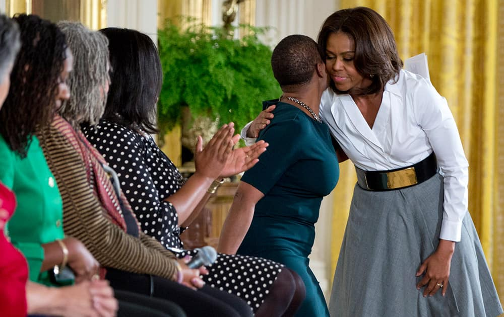 First lady Michelle Obama, embraces Vanessa DeLuca, Editor-in-chief of Essence Magazine as she finishes speaking in the East Room of the White House in Washington.
