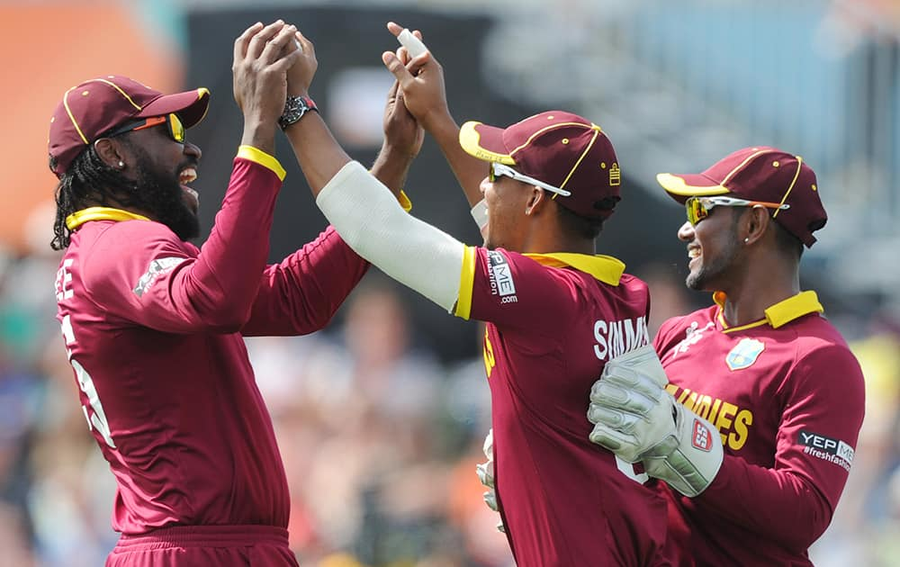 West Indies Lendl Simmons, is congratulated by teammates Chris Gayle and Denesh Ramdin after taking a catch to dismiss Pakistan's Ahmad Shahzad during their Cricket World Cup match in Christchurch, New Zealand.
