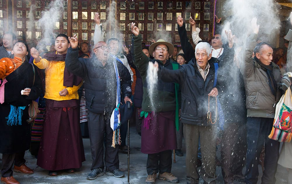 Exile Tibetans throw barley flour into the air at the end of a special morning prayer on the third day of the Tibetan New Year in Dharmsala.