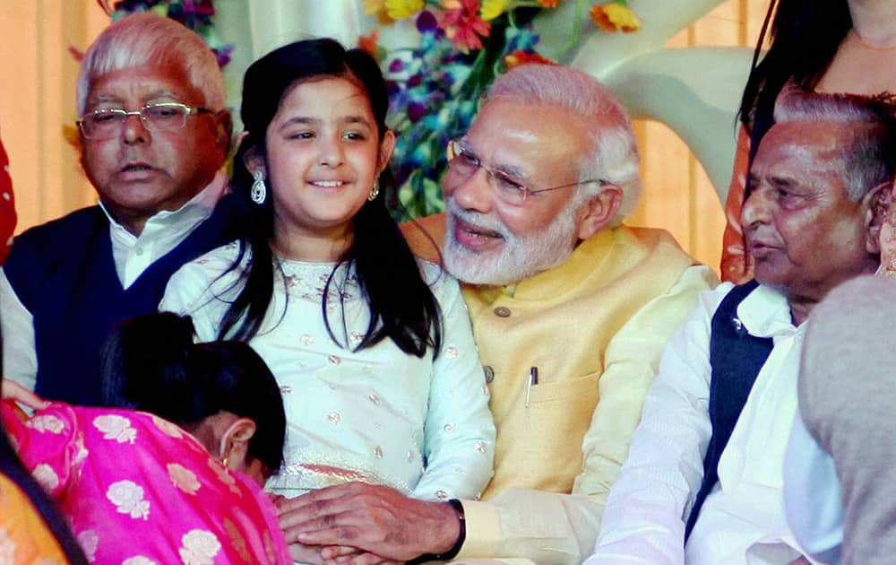 Prime Minister Narendra Modi, holding UP CM Akhilesh Yadavs daughter, attends the Tilakceremony of Tej Pratap Singh Yadav, grand-nephew of Mulayam Singh Yadav (R) and Raj Laxmi, daughter of Lalu Prasad (R), in Saifai..