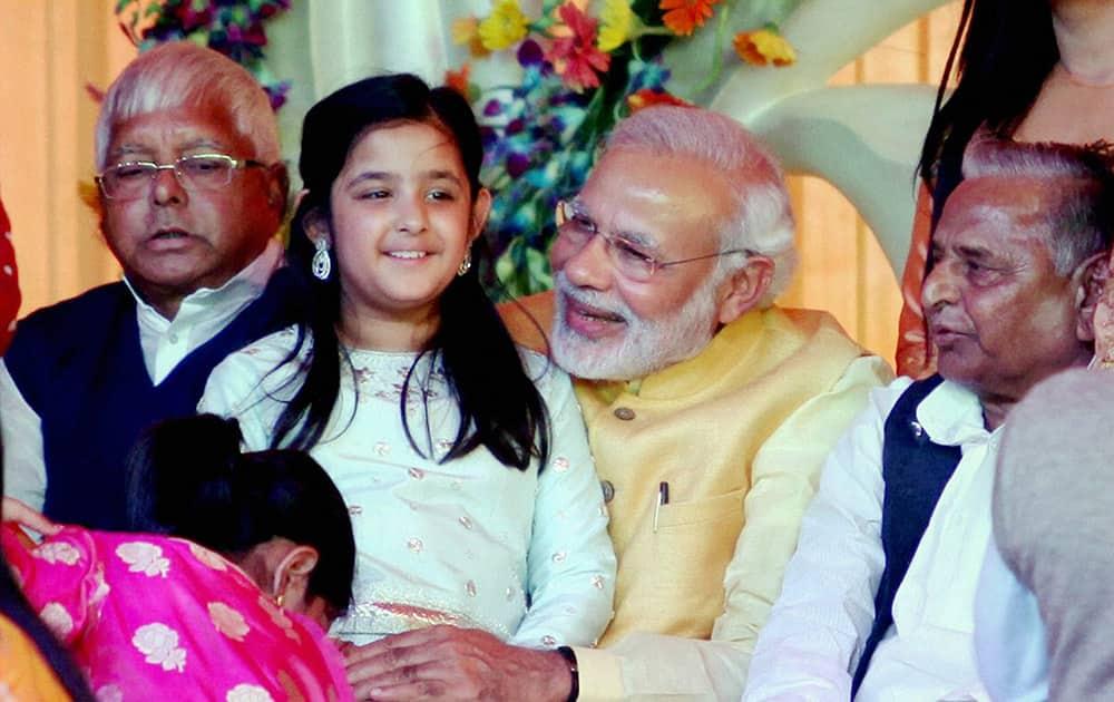 Prime Minister Narendra Modi, holding UP CM Akhilesh Yadavs daughter, attends the Tilakceremony of Tej Pratap Singh Yadav, grand-nephew of Mulayam Singh Yadav and Raj Laxmi, daughter of Lalu Prasad (R), in Saifai.