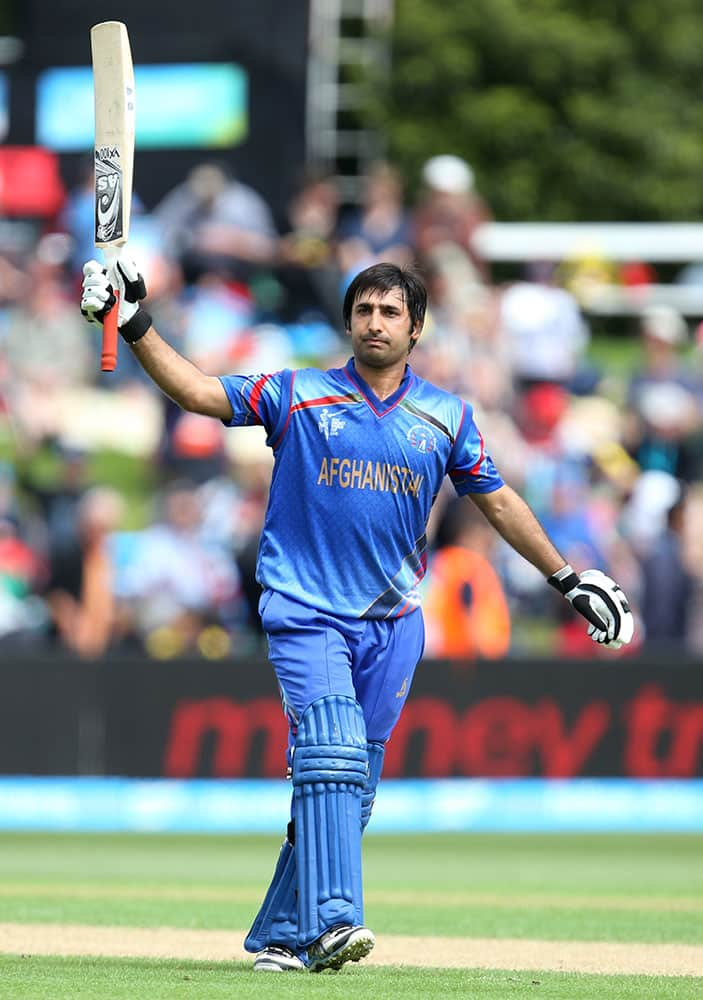 Afghanistan's Asghar Stanikzai waves his bat to the crowd after reaching 50 runs during their Cricket World Cup match against Sri Lanka in Dunedin, New Zealand.