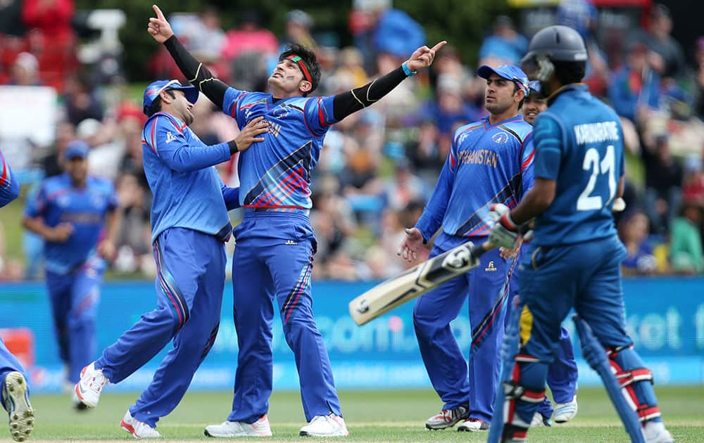 Afghanistan's Hamid Hassan, second left, celebrates after dismissing Sri Lankan batsman Kumar Sangakkara, not pictured, during their Cricket World Cup match in Dunedin, New Zealand.