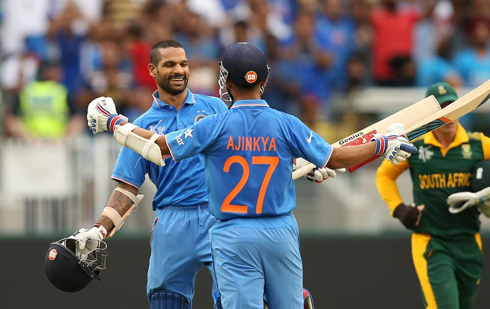India's Shikhar Dhawan celebrates his hundred runs with teammate Ajinkya Rahane, back to camera during their Cricket World Cup pool B match against South Africa in Melbourne, Australia.