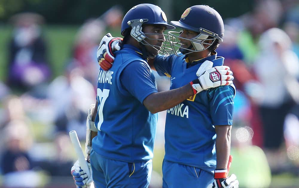 Sri Lanka's Mahela Jayawardena, left, is congratulated by teammate Jeewan Mendis after scoring century during their Cricket World Cup match against Afghanistan in Dunedin, New Zealand.