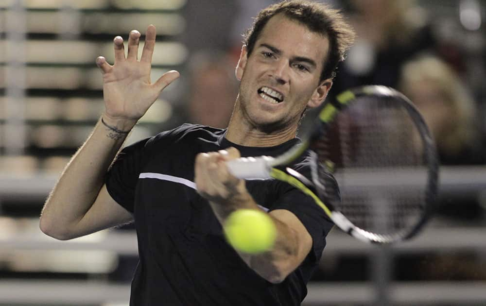 Adrian Mannarino of France, returns the ball to Ivo Karlovic, of Croatia, during a semi-final tennis match at the Delray Beach Open.