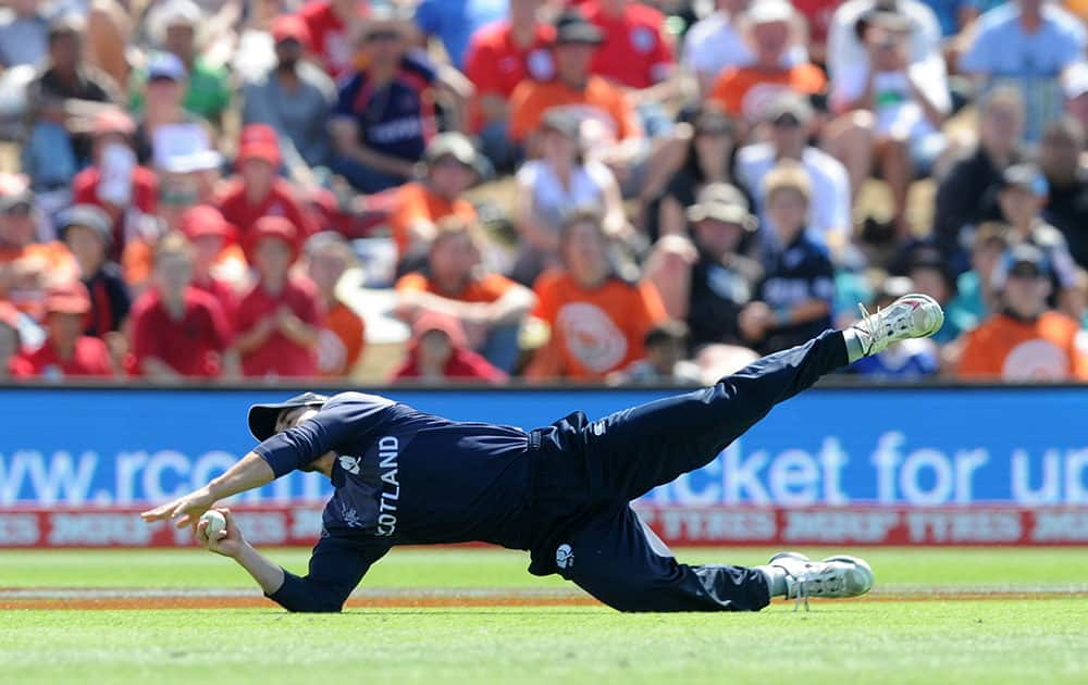 Scotland's Preston Mommsen takes a catch to dismiss England's captain Eoin Morgan during their Cricket World Cup match in Christchurch, New Zealand.