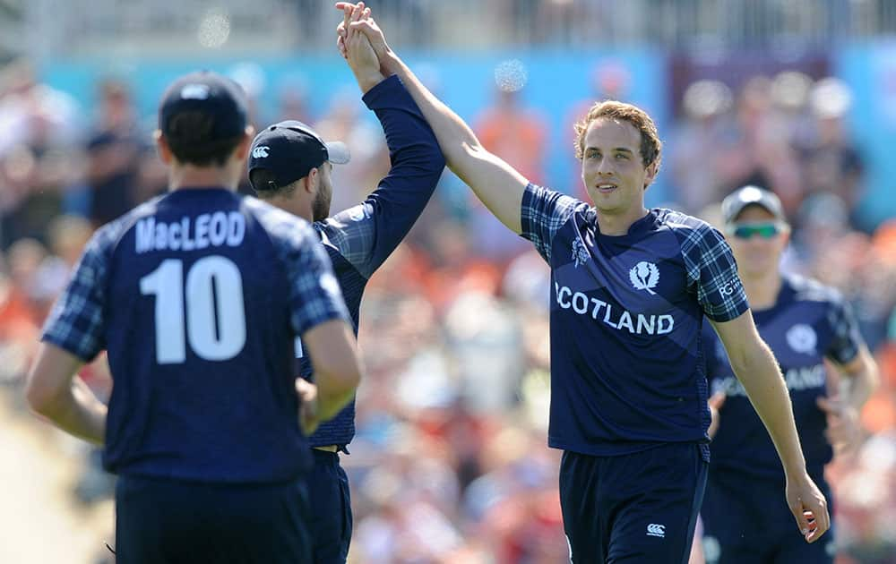 Scotland's Josh Davey, right, is congratulated by teammates after taking a wicket during their Cricket World Cup match against England in Christchurch, New Zealand.