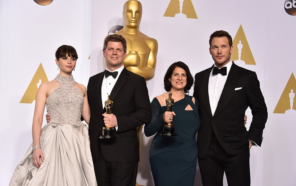 """Felicity Jones, and from left, Adam Stockhausen, Anna Pinnock and Chris Pratt pose in the press room with the award for best production design for """"The Grand Budapest Hotel"""" at the Oscars."""