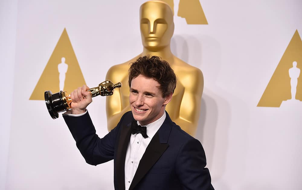 """Eddie Redmayne poses in the press room with the award for best actor in a leading role for """"The Theory of Everything"""" at the Oscars."""