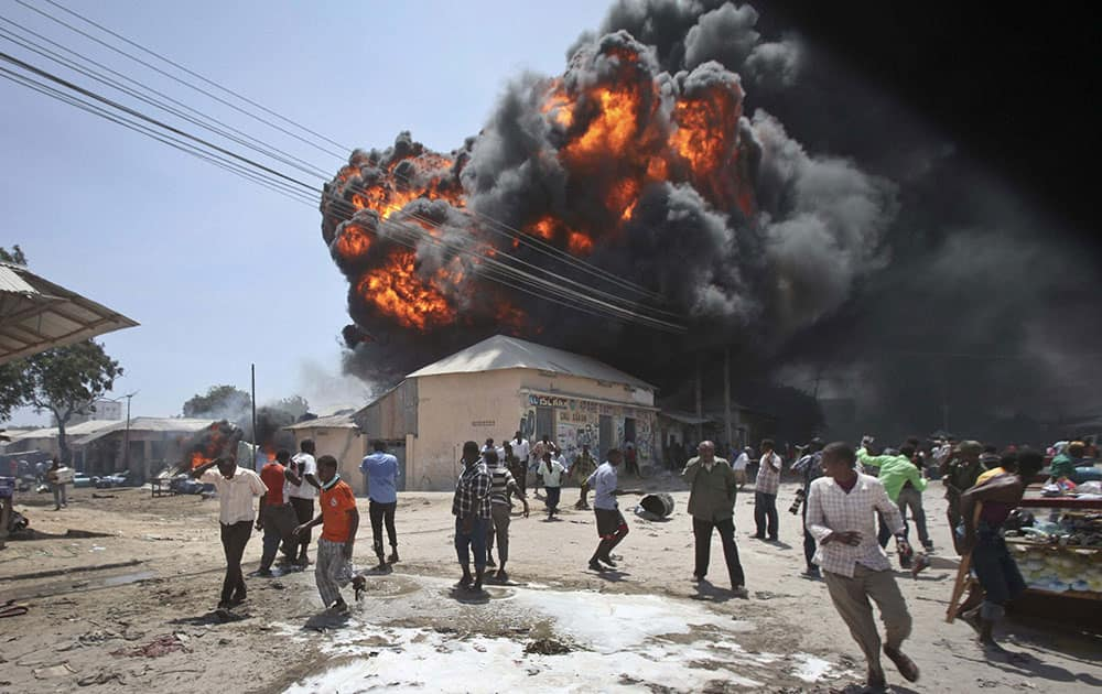 Somalis run from an explosion during a fire that engulfed a fuel market, causing extensive property damage but no loss of life, in the Hodan district of the capital Mogadishu, Somalia.