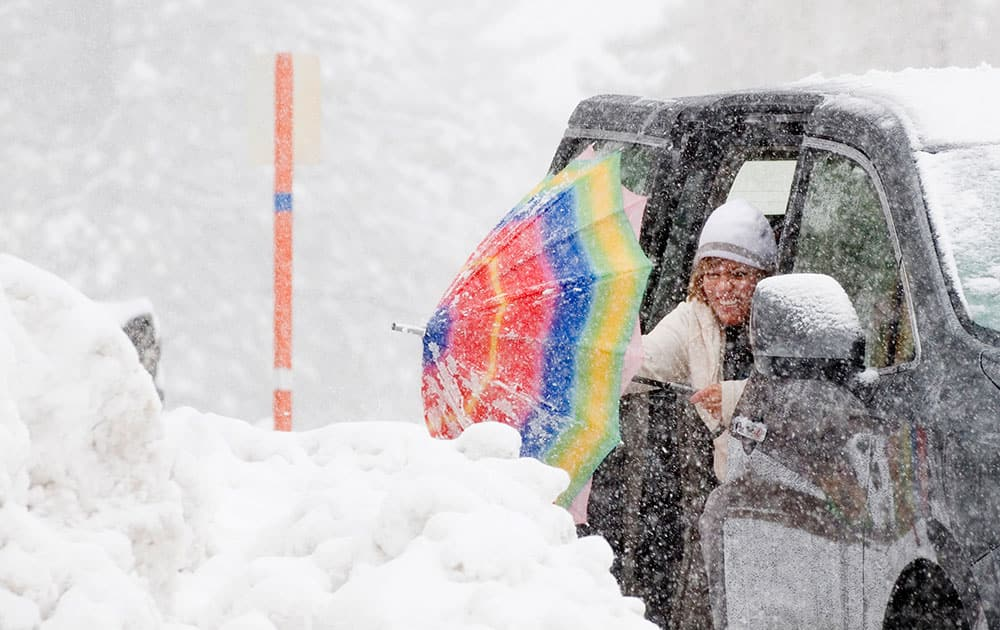 Carmen Lopez, of Palmdale, Calif., shakes snow from her umbrella, in Wrightwood, Calif.