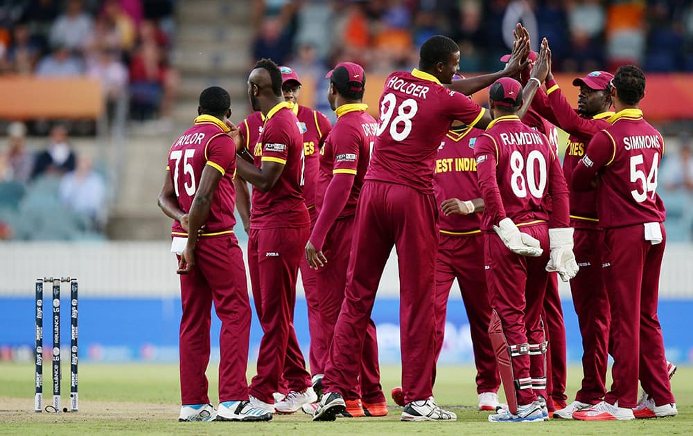 West Indies team celebrate after the dismissal of Zimbabwe's Regis Chakabva during their Cricket World Cup Pool B match in Canberra, Australia.